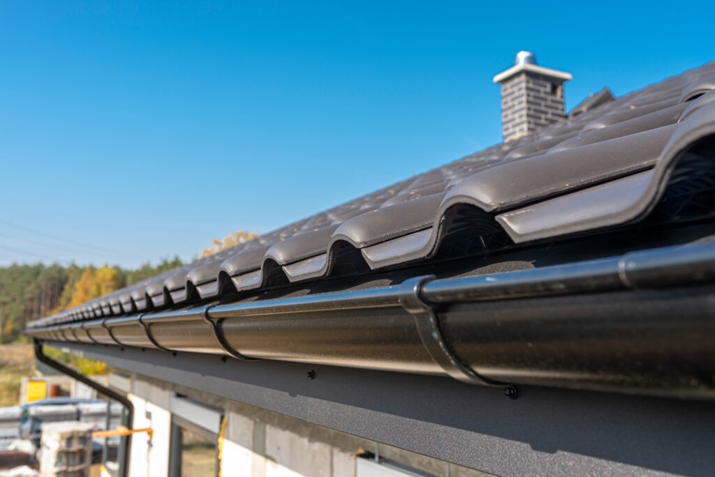 Metal-Black-Qutter-On-A-Roof-Covered-With-Cerami